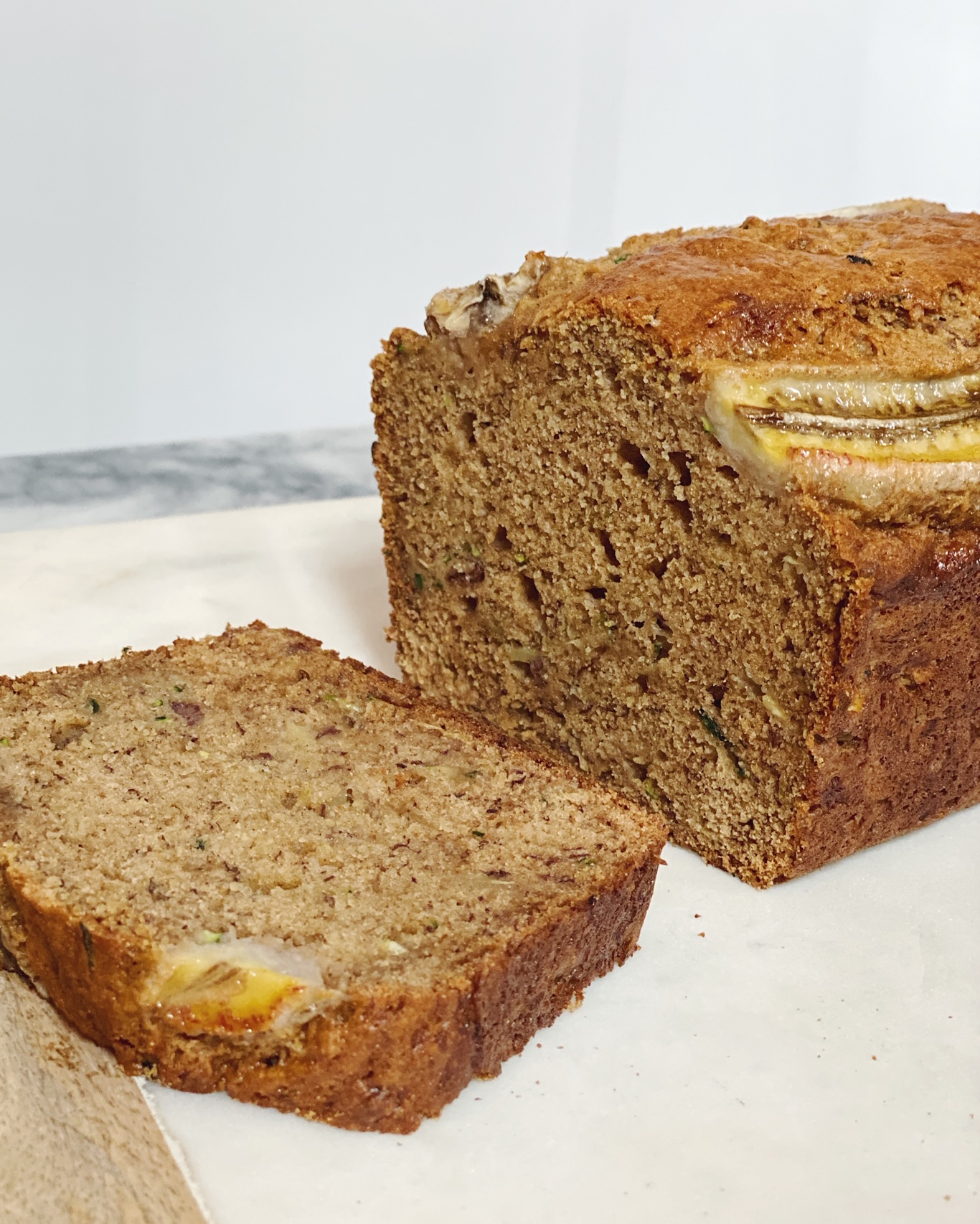 Loaf of banana bread with one slice cut