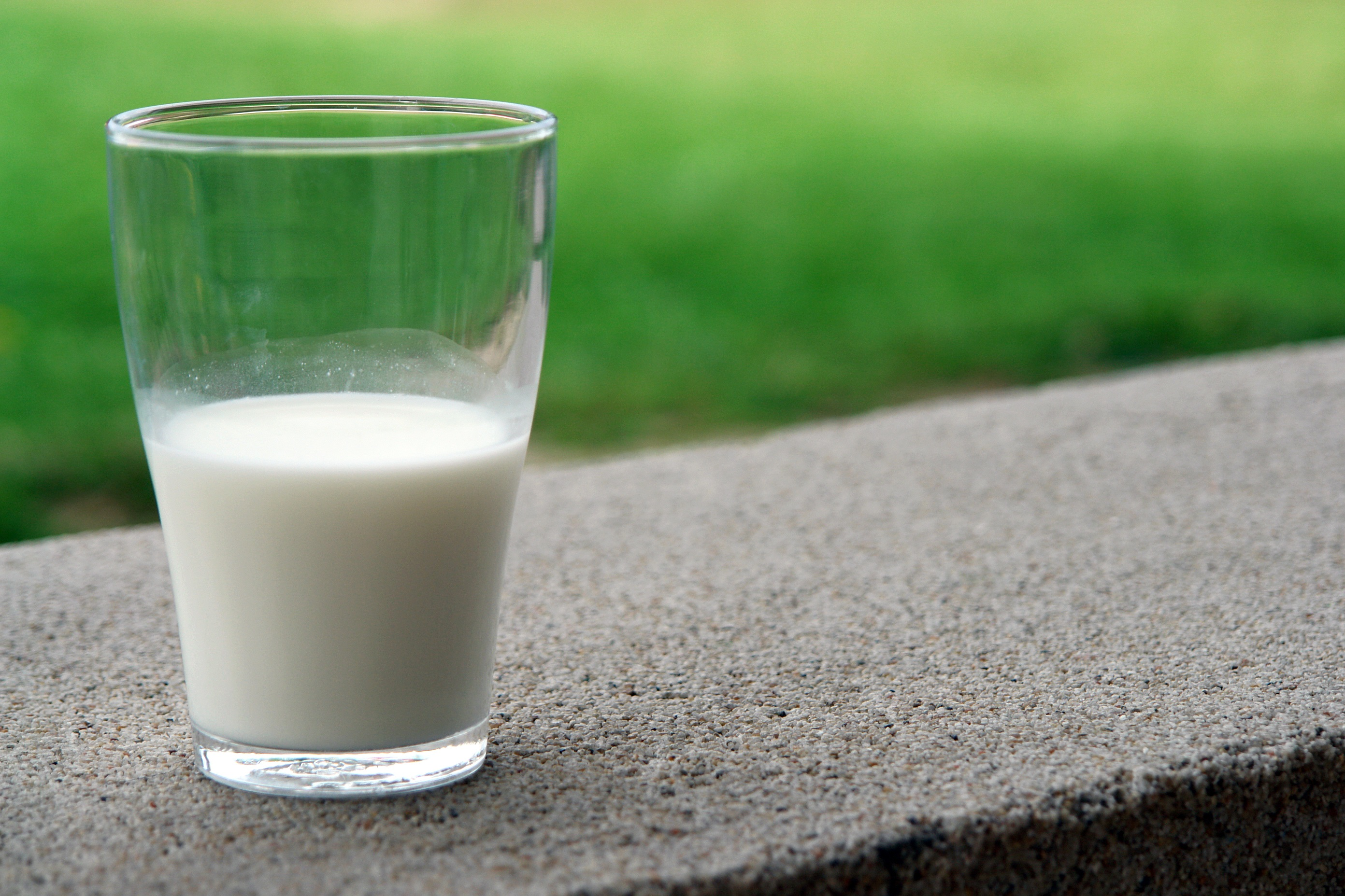 Glass half-full of milk outside